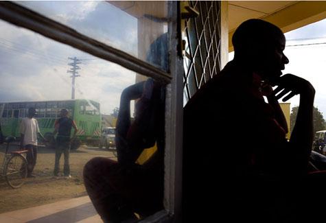 Man sitting by a window at a bus stop, Rwanda